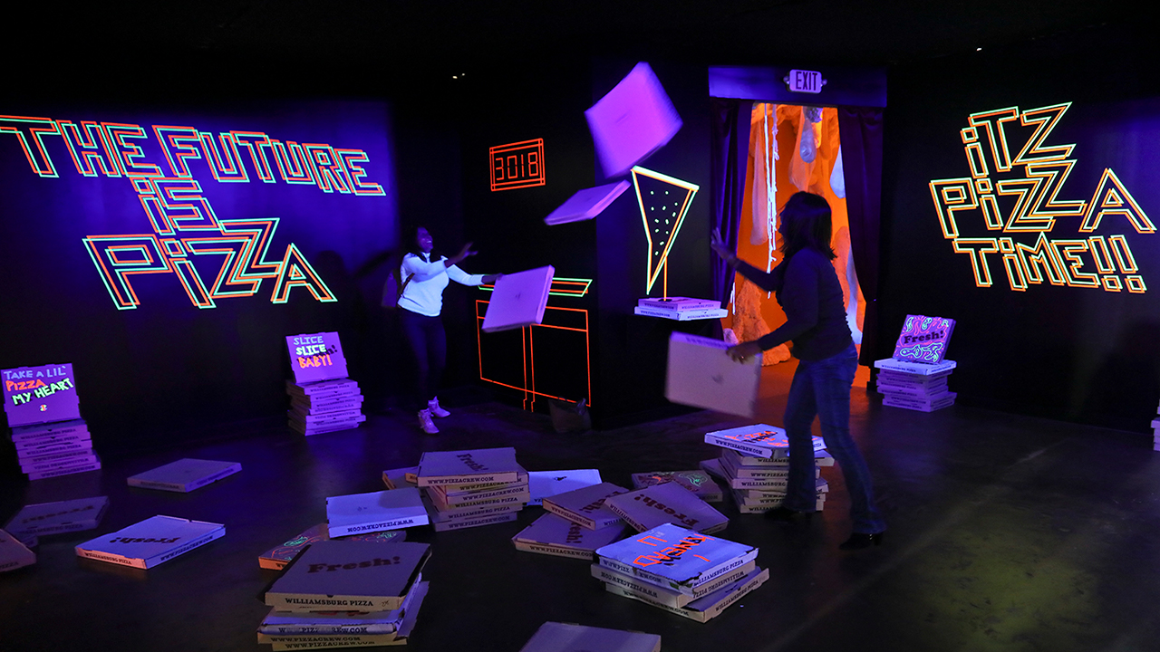 This photo shows a pizza box playroom created with neon lights and colorful fluorescent tape called Gazoo, part of a group art exhibition celebrating pizza..