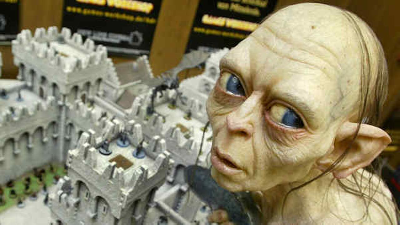 Gollum sits above a model of the town Minas Tirith during a press presentation for the Spiel 03 fair in Essen, Germany