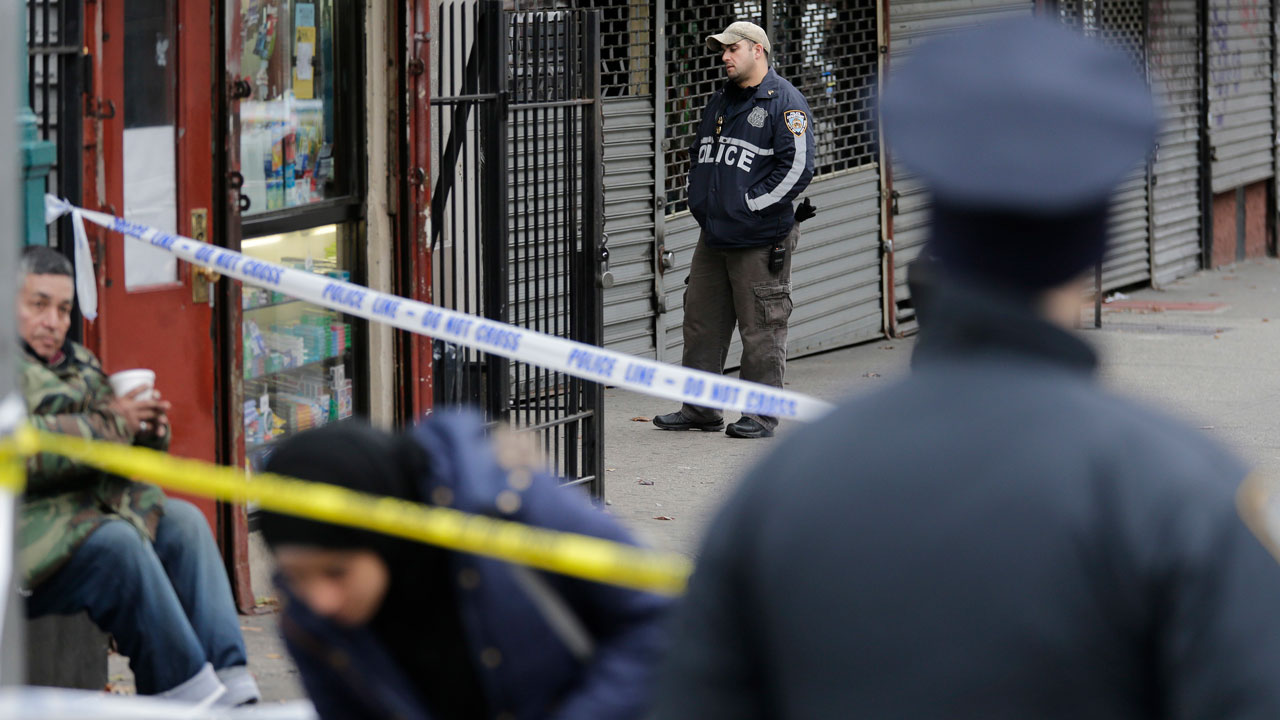 FILE: As police officers stand nearby, pedestrians make their way through crime scene tape at the scene of a shooting in the Bronx section of New York, Tuesday, Dec. 5, 2017.