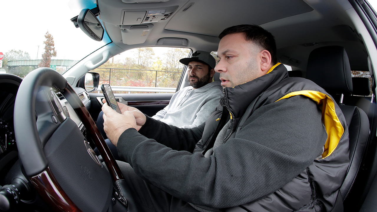 Lenny Sciascia, right, and his friend Mario DeAngelis look at betting lines for the days sporting events before placing bets in a parking lot just off the Bayonne Bridge.