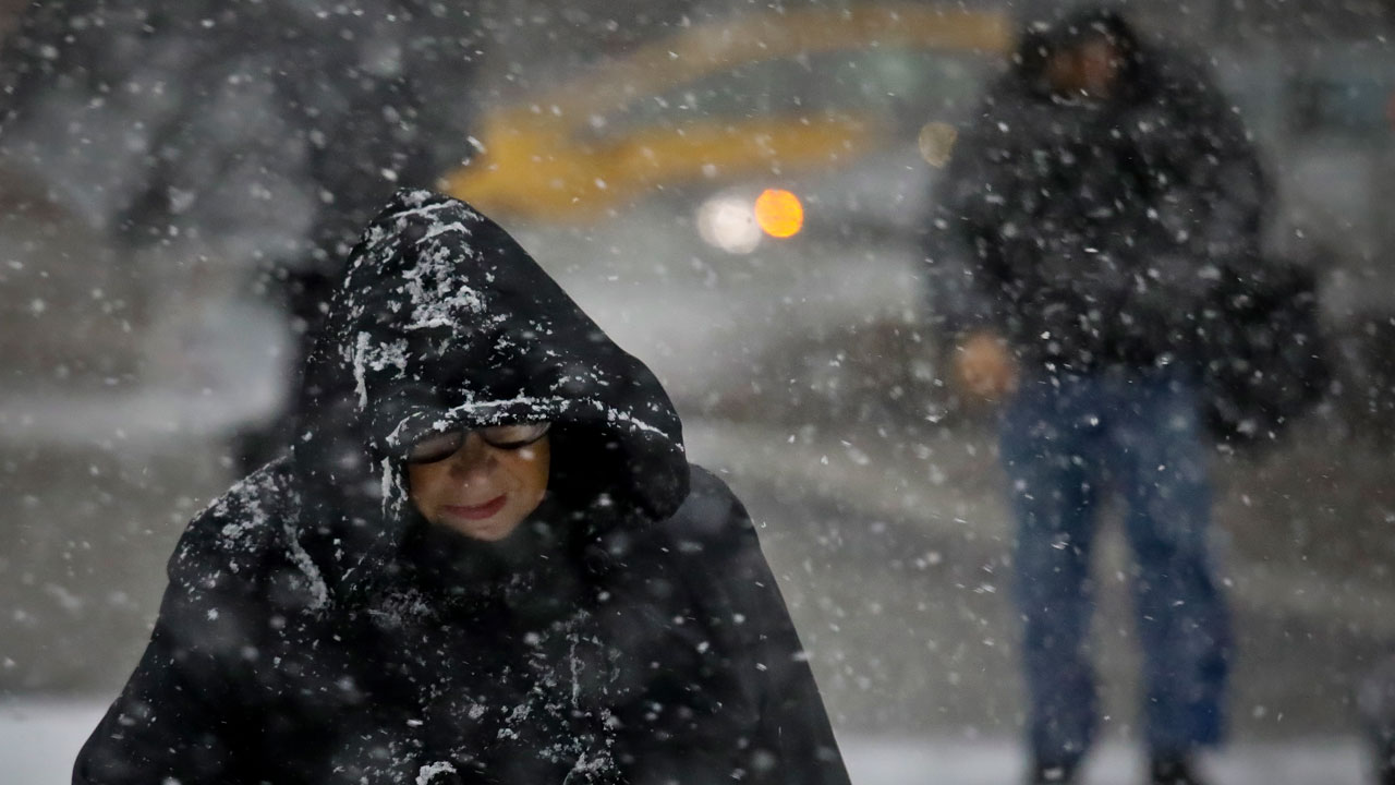 Pedestrians face a wet snowfall in lower Manhattan, Thursday Nov. 15, 2018, in New York.