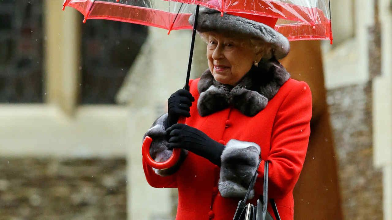 Queen Elizabeth II shelters under an umbrella as she leaves after attending the British royal familys traditional Christmas Day church service.