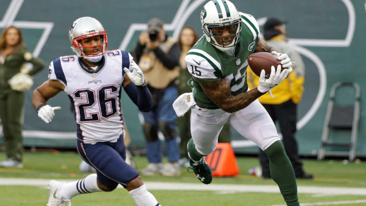 New York Jets wide receiver Brandon Marshall (15) catches a pass for a touchdown in front of New England Patriots Logan Ryan.