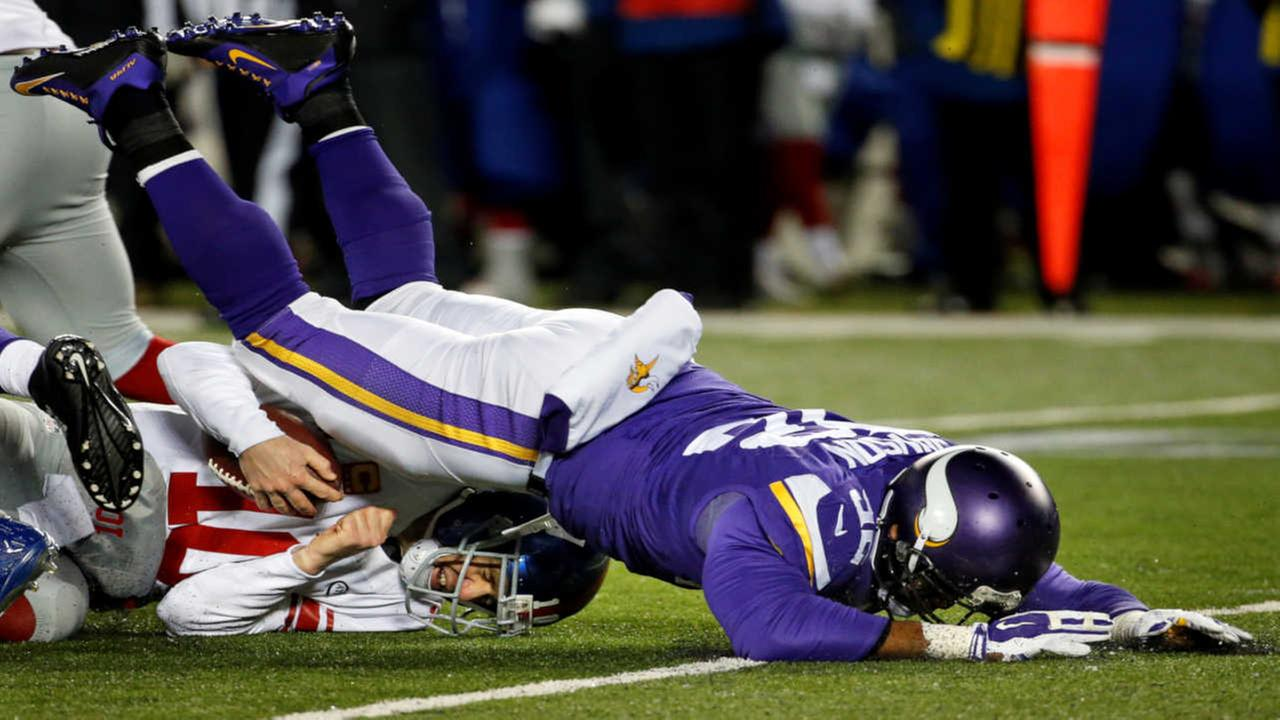 Minnesota Vikings defensive tackle Tom Johnson, right, sacks New York Giants quarterback Eli Manning during the first half of an NFL football game, Sunday, Dec. 27, 2015.