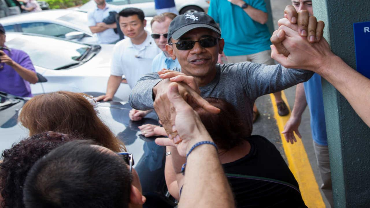 President Barack Obama shakes hands with bystanders during a visit to Island Snow during a family vacation on Sunday, Dec. 27, 2015, in Kailua, Hawaii.