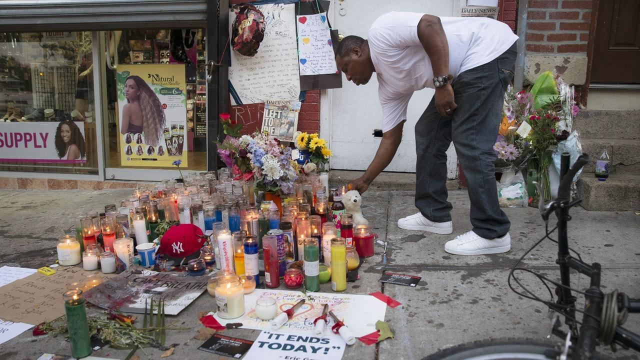 In this July 22, 2014, file photo, a mourner places a candle at a memorial for Eric Garner, who died while being arrested by New York City police, in Staten Island.