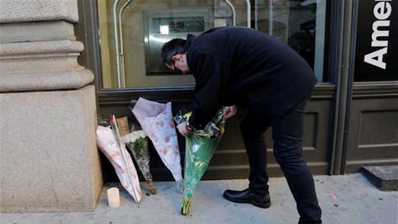 Nick Zieminski places a bouquet of flowers in front of the building where David Bowie had his New York apartment. AP Photo/Mark Lennihan)
