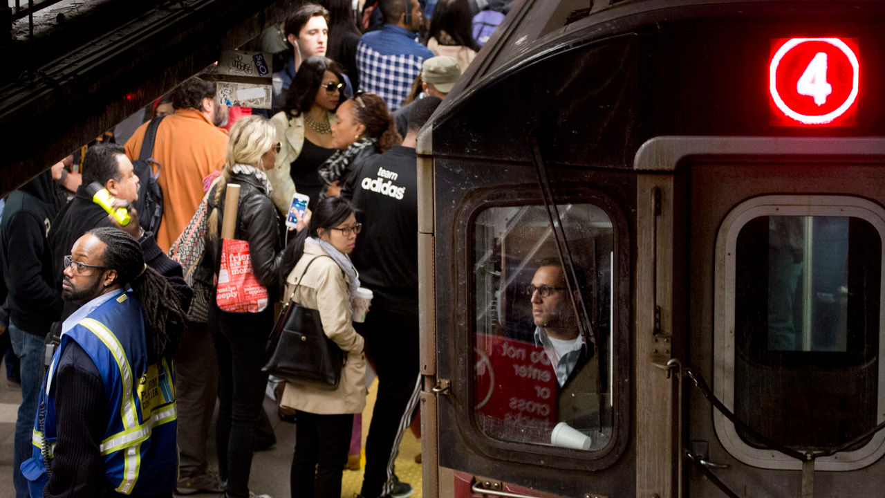 In this May 10, 2016 photo, commuters wait to get on the 4 subway train in the Union Square station in New York.
