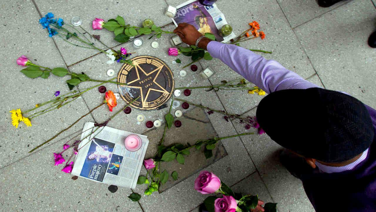 Tim Morfon place flowers over musician Princes star on a makeshift memorial on the sidewalk outside of the Warner Theatre in Washington Friday.