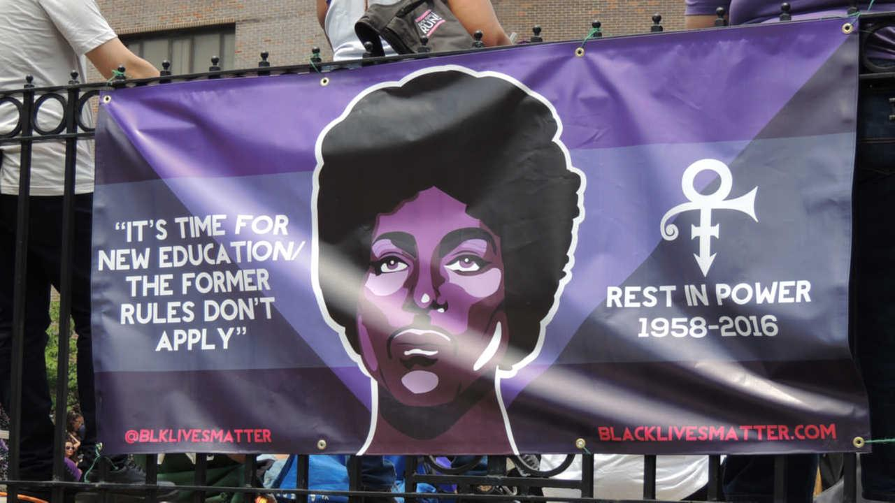 A poster bearing the likeness of the entertainer is attached to a railing at the Prince Born Day Purple People Party in New York, Saturday, June 4, 2016.