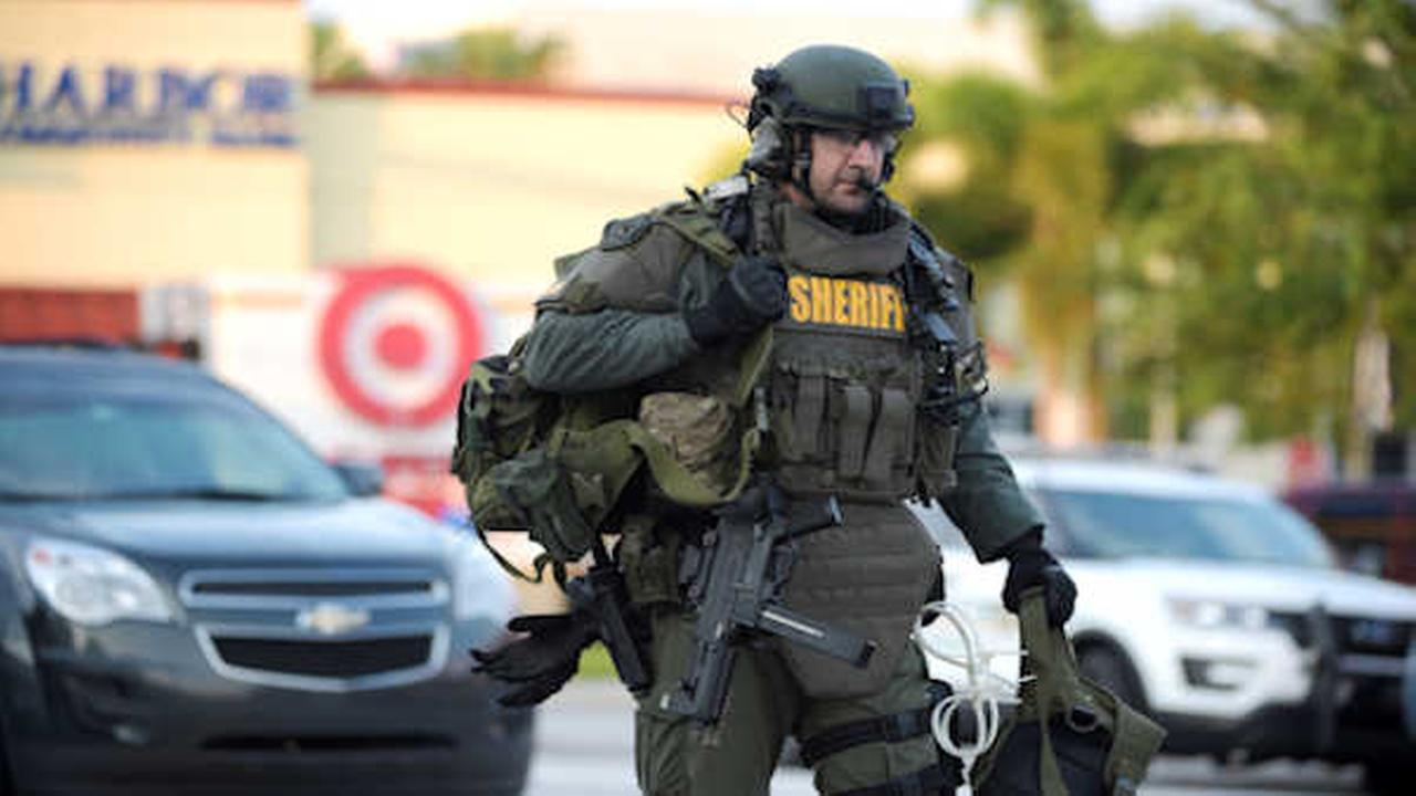An Orange County Sheriffs Department SWAT member arrives to the scene of a fatal shooting at Pulse Orlando nightclub in Orlando, Fla., Sunday, June 12, 2016. (AP Photo/Phelan M. E