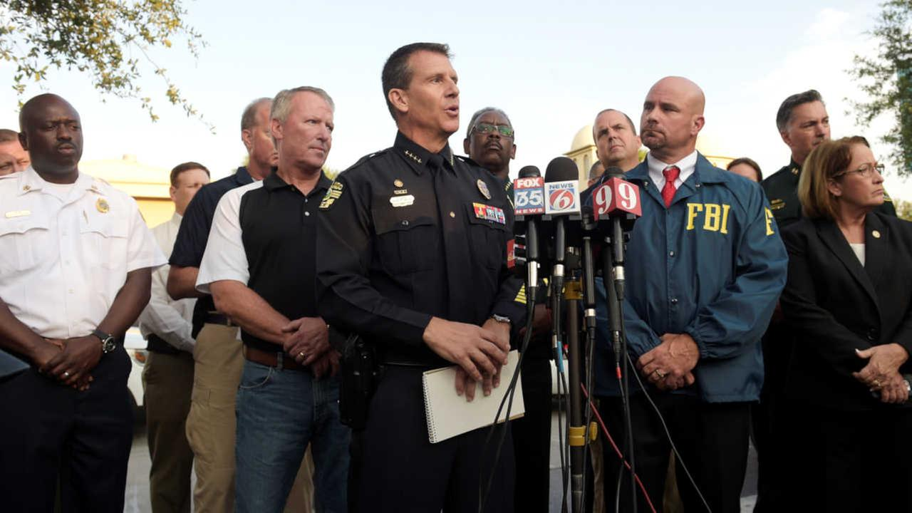 Orlando Police Chief John Mina, center, addresses reporters during a news conference after a shooting involving multiple fatalities at a nightclub in Orlando, Fla., Sunday, June 12