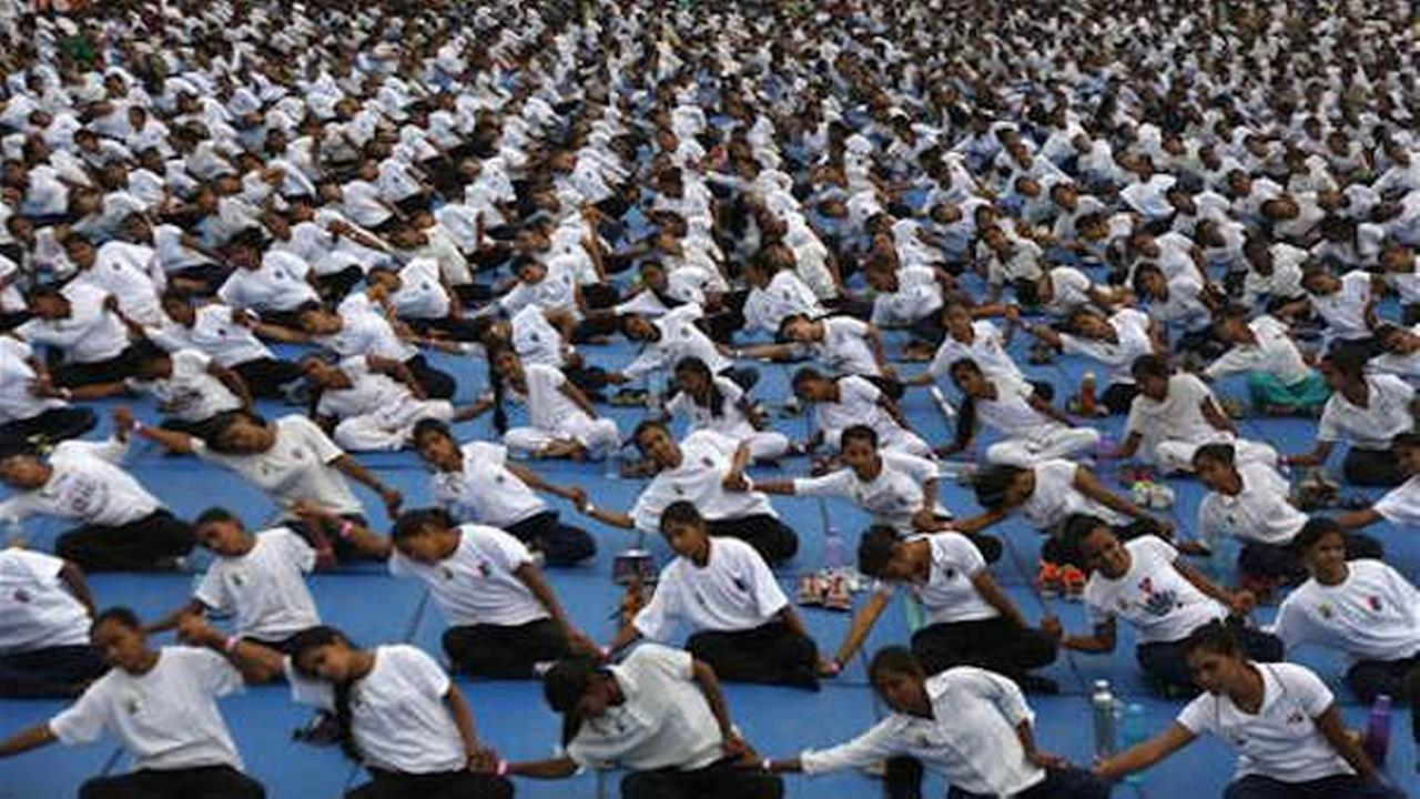 Indians holds hands as they attempt to create a record for the longest human yoga chain with more than 8000 participants. (AP Photo/Ajit Solanki)
