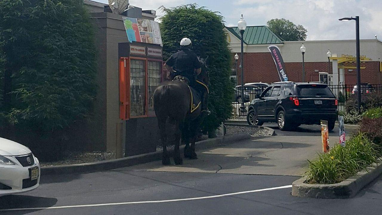 Mounted police officer rides through Dunkin' Donuts drive-thru on horseback