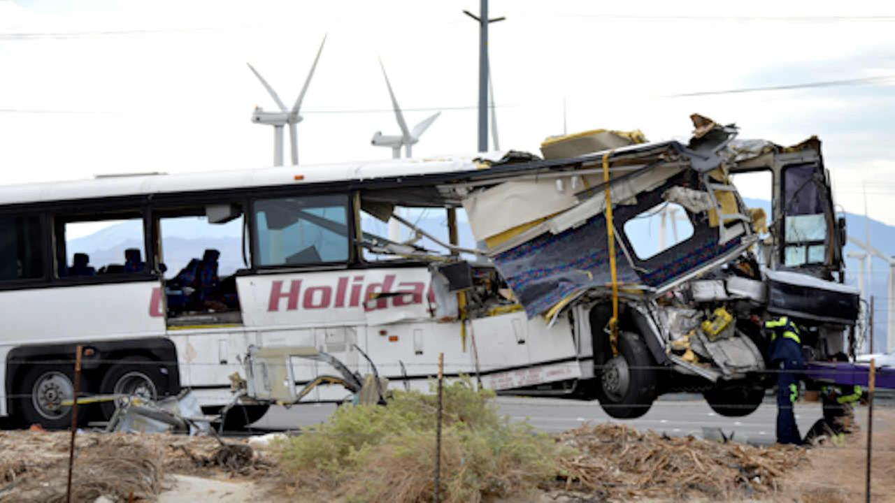Workers prepare to haul away a tour bus that crashed with semi-truck on Interstate 10 near Palm Springs.   (AP Photo/Rodrigo Pena)