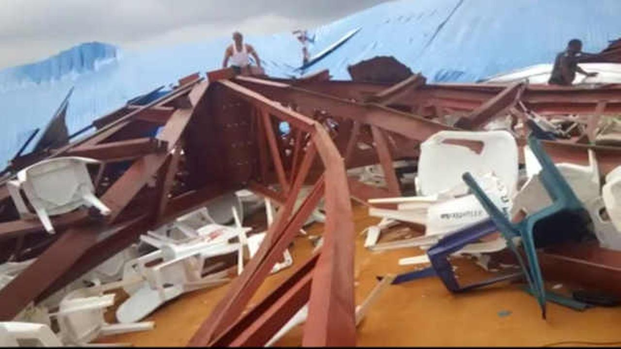 In this image made from video taken on Saturday, Dec. 10, 2016, local people survey the scene after a church roof collapsed in Uyo, Nigeria. (Ukeme Eyibio via AP)