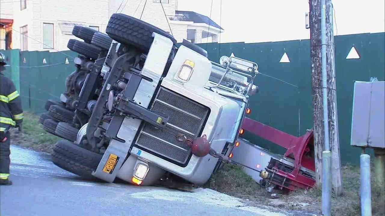 A truck hauling a crane overturned on an icy road in Queens Thursday morning.