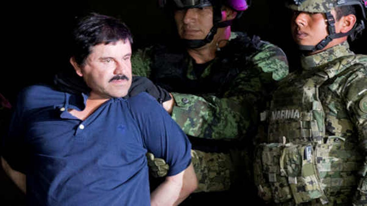 In this Jan. 8, 2016 file photo, a handcuffed Joaquin El Chapo Guzman is made to face the press as he is escorted to a helicopter by Mexican soldiers and marines