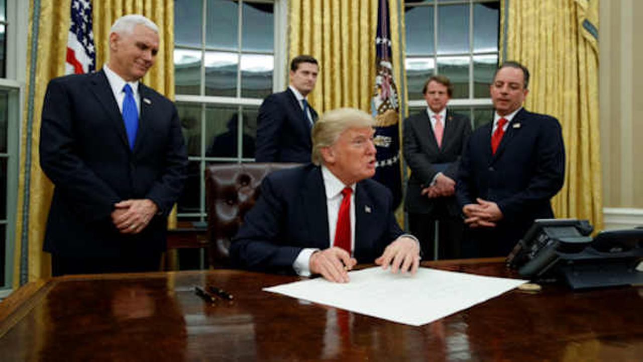 President Donald Trump prepares to sign his first executive order, Friday, Jan. 20, 2017, in the Oval Office of the White House in Washington. (AP Photo/Evan Vucci)