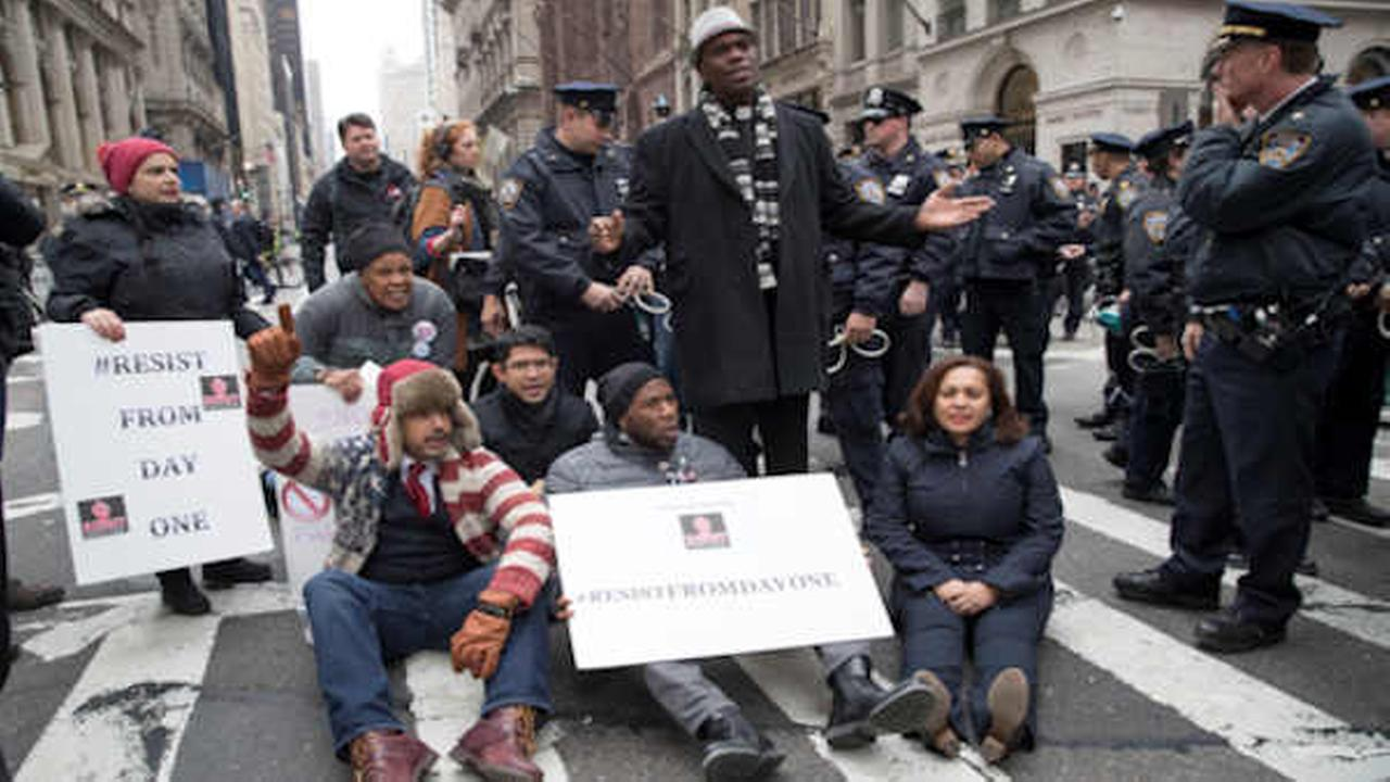 Police officers prepare to take New York City Councilman Jumaane Williams, center, into custody after he and others blocked traffic outside Trump Tower   (AP Photo/Mary Altaffer)
