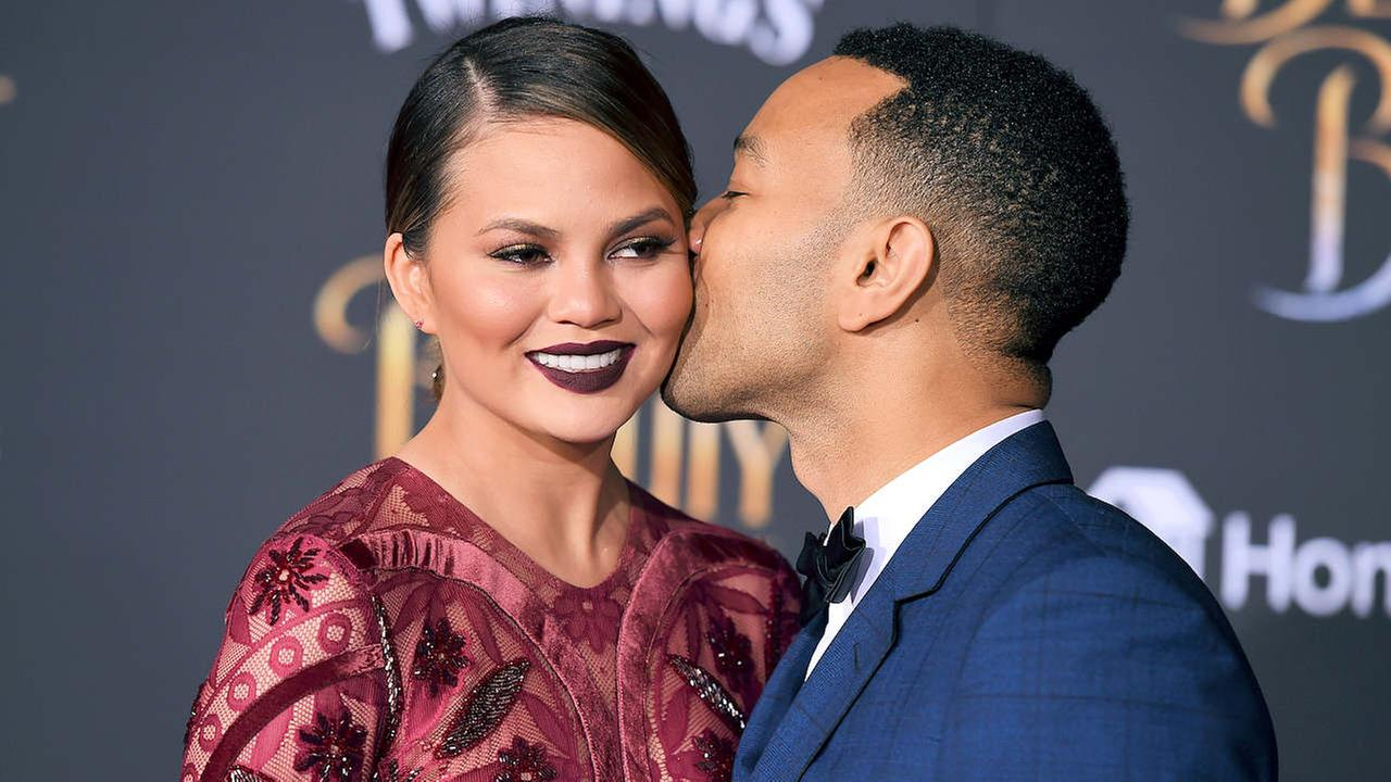 John Legend, right, kisses Chrissy Teigen as they arrive at the world premiere of Beauty and the Beast at the El Capitan Theatre on Thursday, March 2, 2017, in Los Angeles.