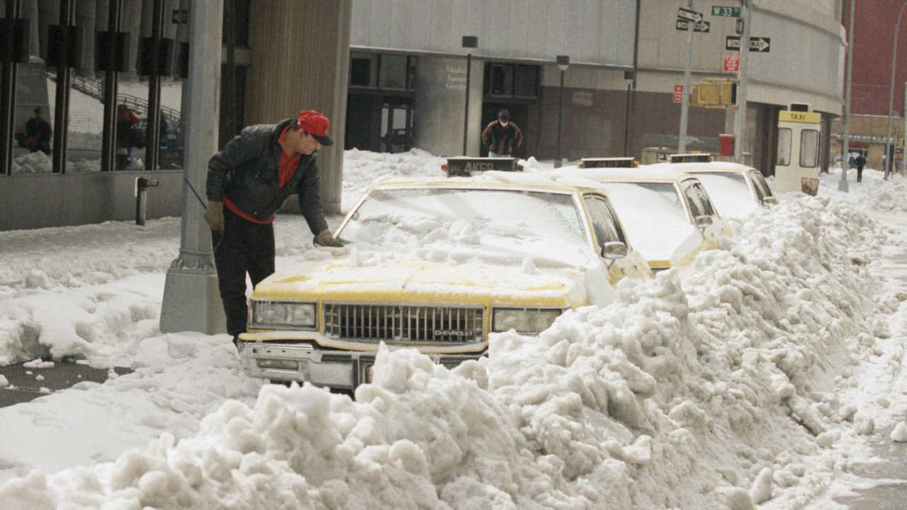 A nNew York City taxi driver tries to free his cab from snow piled up by street plows early Sunday morning March 15, 1993.