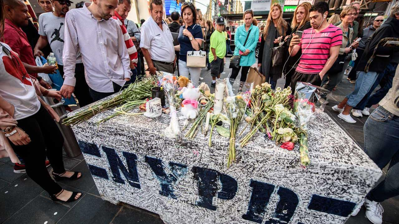 A concrete barrier at the intersection of 45th Street and Seventh Avenue in Times Square has been turned into a makeshift memorial for the victims of a deadly pedestrian crash.