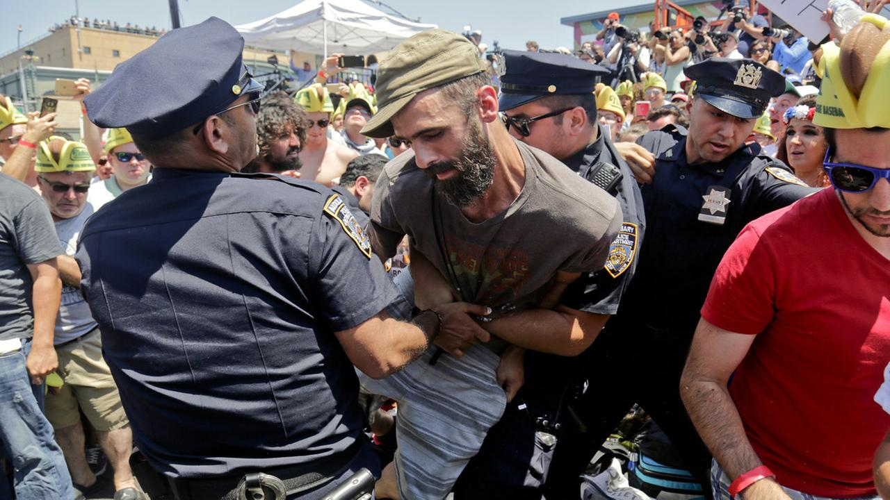 Police remove an animal rights activist as they try to protest at the Nathans Annual Famous International Hot Dog Eating Contest won by Joey Chestnut, Tuesday July 4, 2017.
