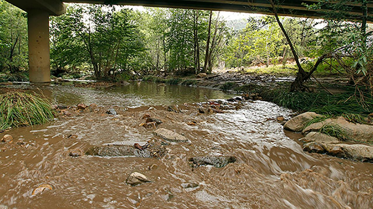 Muddy floodwaters of the East Verde River flow under a bridge where one victim of the flash flood was found during a search and rescue operation (AP Photo/Ralph Freso)