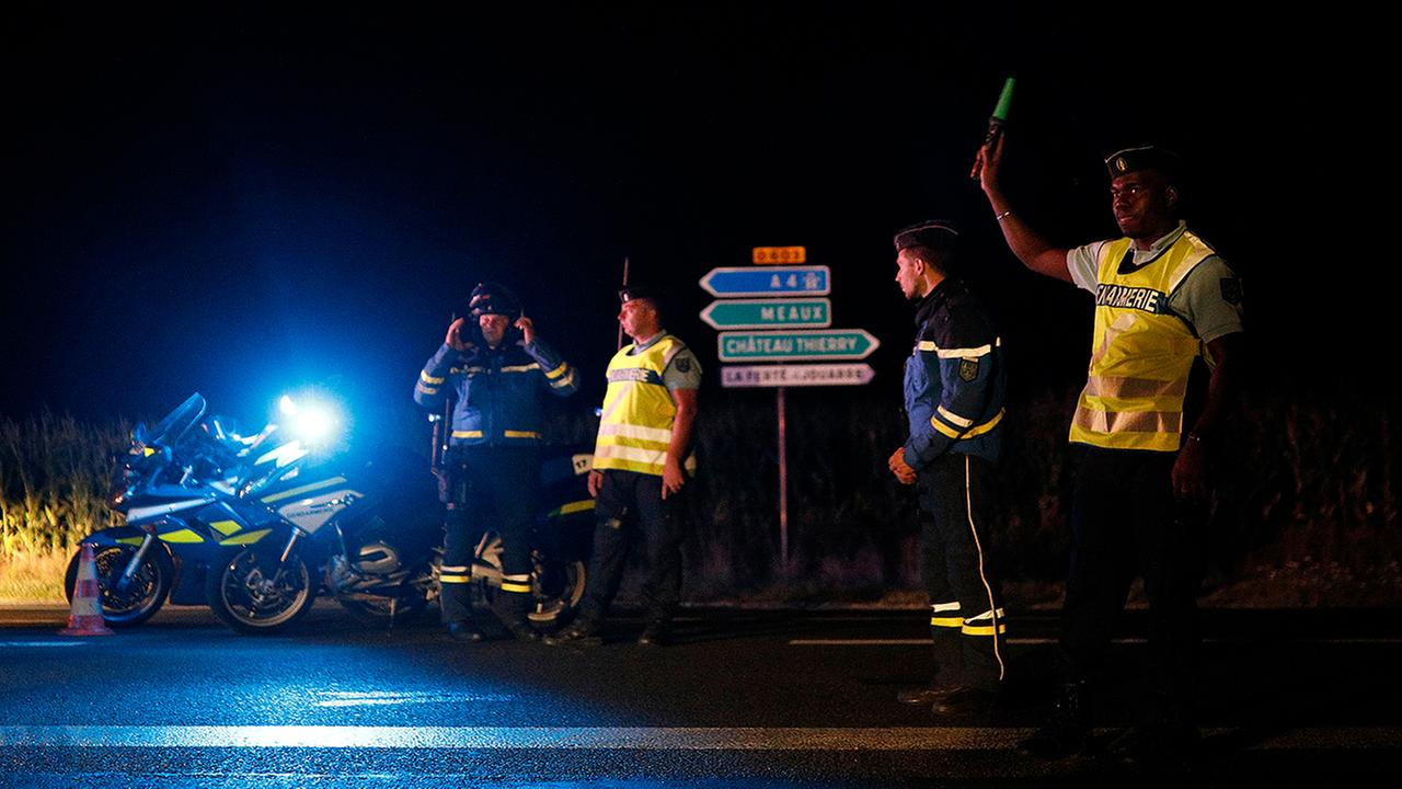 Police officers block the road approaching the scene of an incident when a driver slammed his car into the sidewalk cafe of a pizza restaurant (AP Photo/Kamil Zihnioglu)