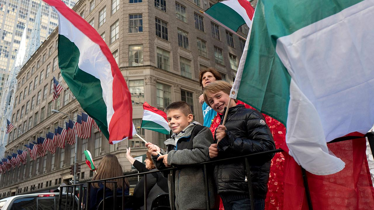 Boys wave Italian flags while riding a float in the Columbus Day Parade, Monday, Oct. 10, 2016, in New York. (AP Photo/Mark Lennihan)
