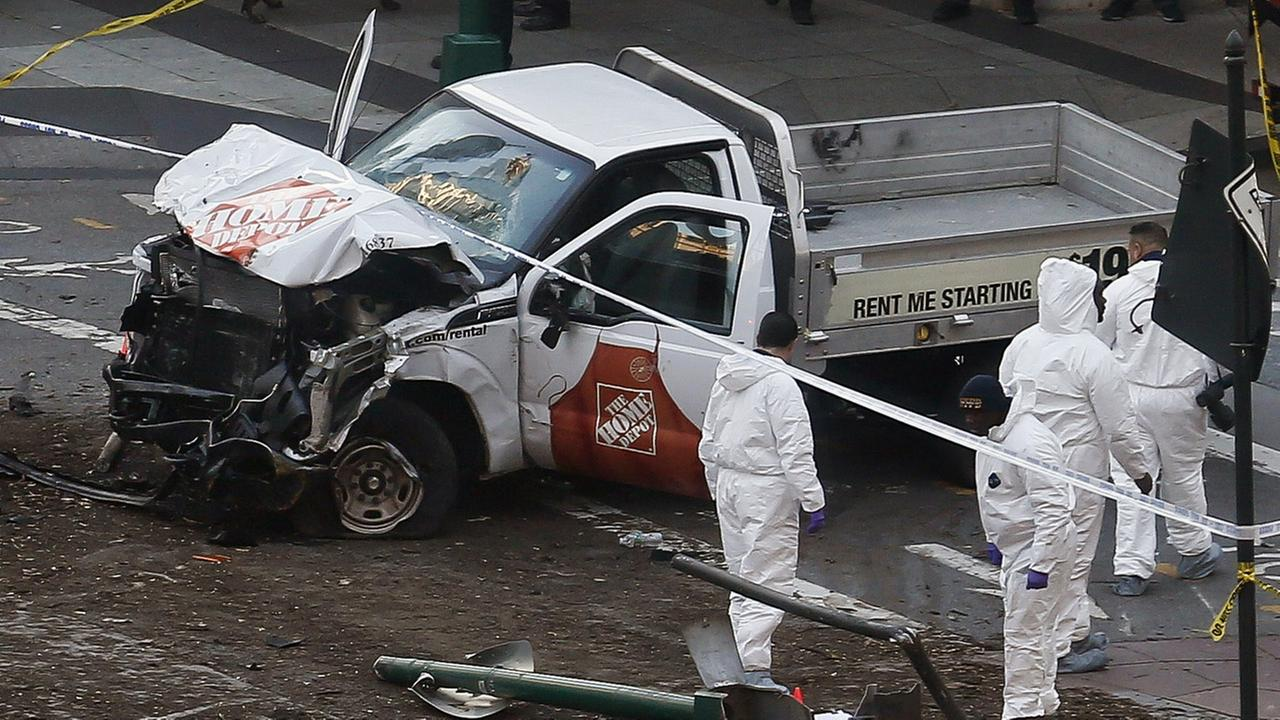 Authorities stand near a damaged Home Depot truck after a motorist drove onto a bike path near the World Trade Center memorial, striking and killing several people Oct. 31, 2017.