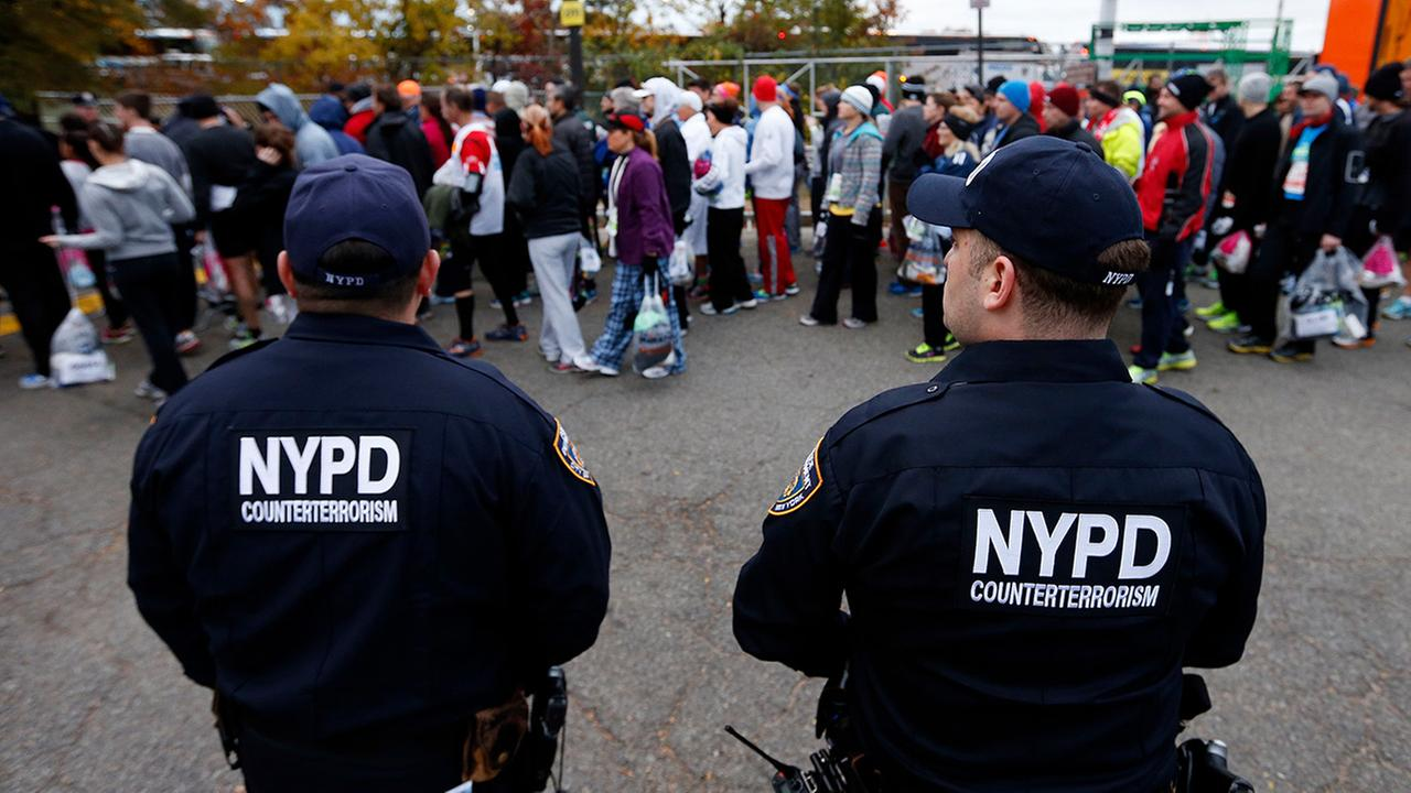In this file photo, police officers from the counterterrorism unit stand watch over runners who arrive for the New York City Marathon in New York.