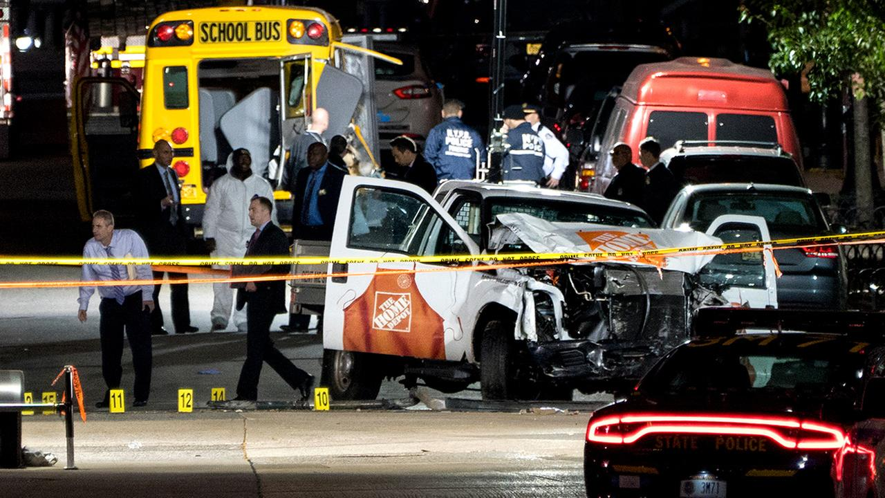 Authorities stand near a damaged Home Depot truck after a motorist drove onto a bike path near the World Trade Center memorial, striking and killing several people Tuesday