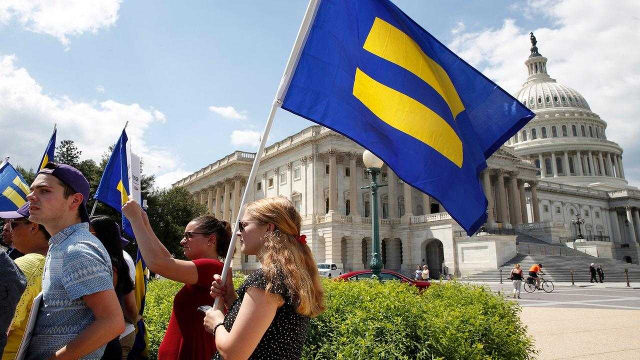 People hold up equality flags on Capitol Hill in Washington, Wednesday, July 26, 2017