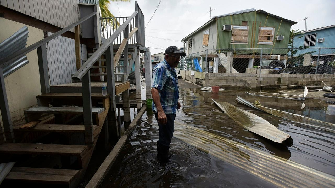 A resident wades through a flooded area in the aftermath of Hurricane Maria, in Catano, Puerto Rico, Wednesday, Sept. 27, 2017.