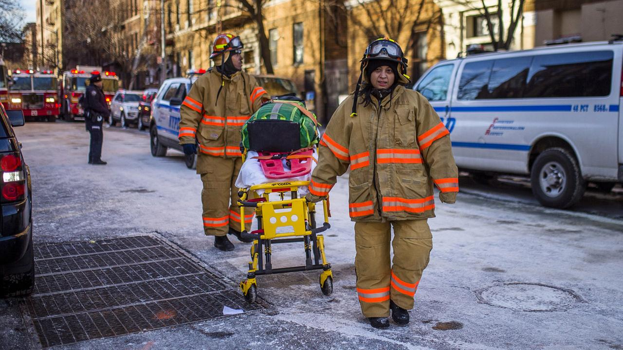 Police stand guard as paramedics leave the scene near the building Friday, Dec. 29, 2017, where more than 10 people died in a fire on Thursday in the Bronx.