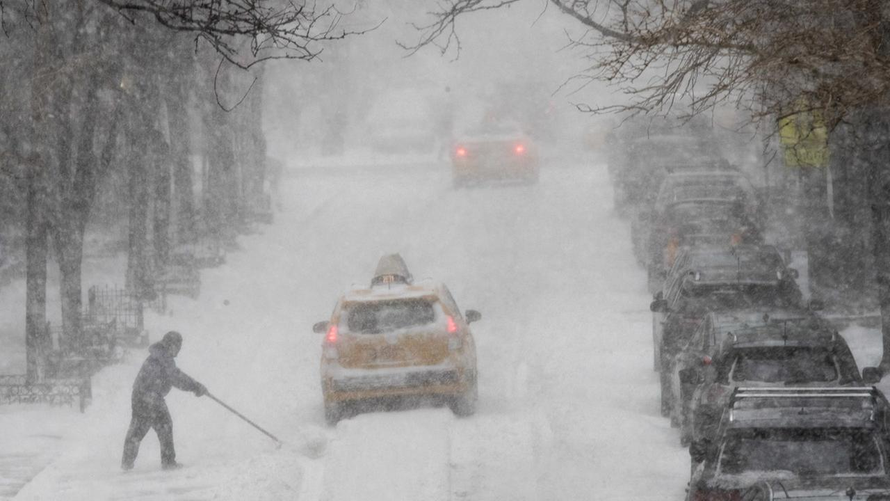 A man shovels snow as traffic makes its way east on 81st street, Thursday, Jan. 4, 2018, on the Upper East Side of Manhattan.