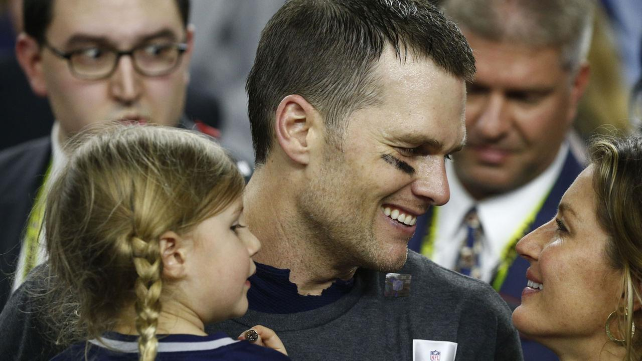 New England Patriots quarterback Tom Brady talks with his wife, Gisele Bundchen (R), as his daughter, Vivian Lake Brady (L) looks on after winning the first overtime Super Bowl.