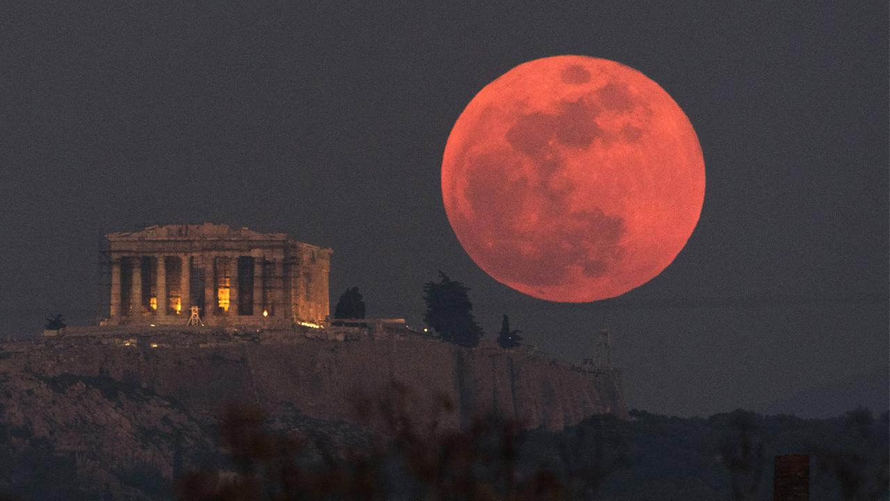 A super blue blood moon rises behind the 2,500-year-old Parthenon temple on the Acropolis of Athens, Greece, on Wednesday, Jan. 31, 2018.