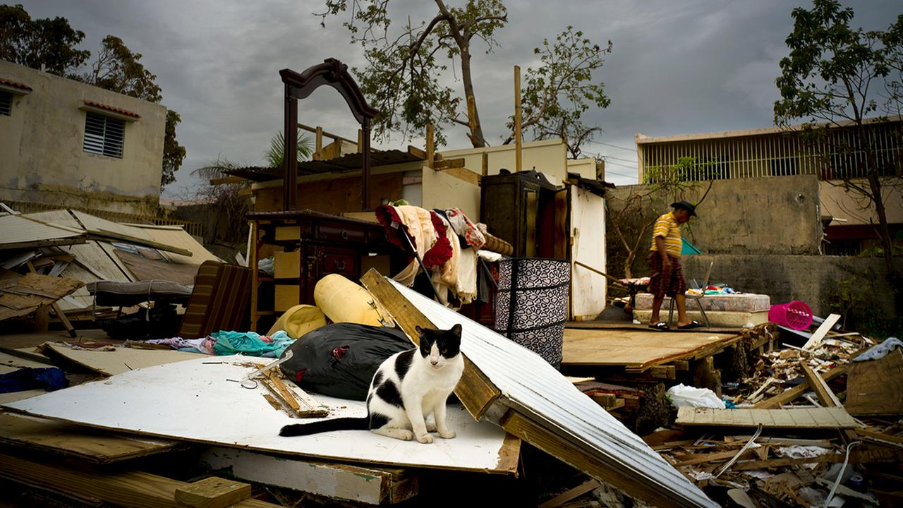 Efrain Diaz Figueroa, right, walks by his sisters home destroyed in the passing of Hurricane Maria, in San Juan, Puerto Rico, Monday, Oct. 9, 2017. (AP Photo/Ramon Espinosa)