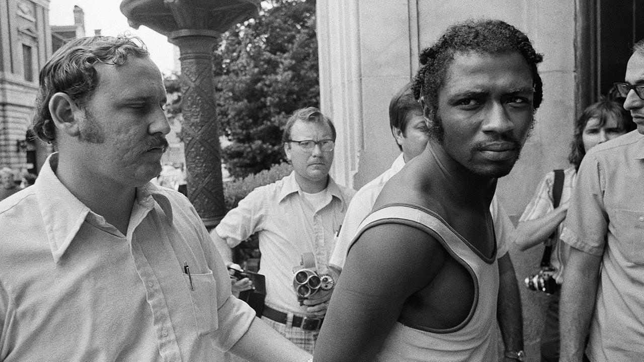 In this Sept. 1, 1973 file photo, Herman Bell, right, glares at the media following his arrest in New Orleans.