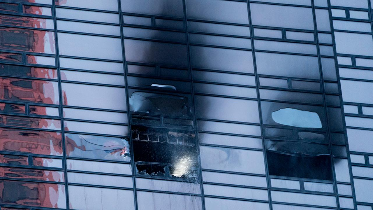 Water pours from the window of a fire damaged apartment in Trump Tower Saturday, April 7, 2018, in New York. (AP Photo/Craig Ruttle)