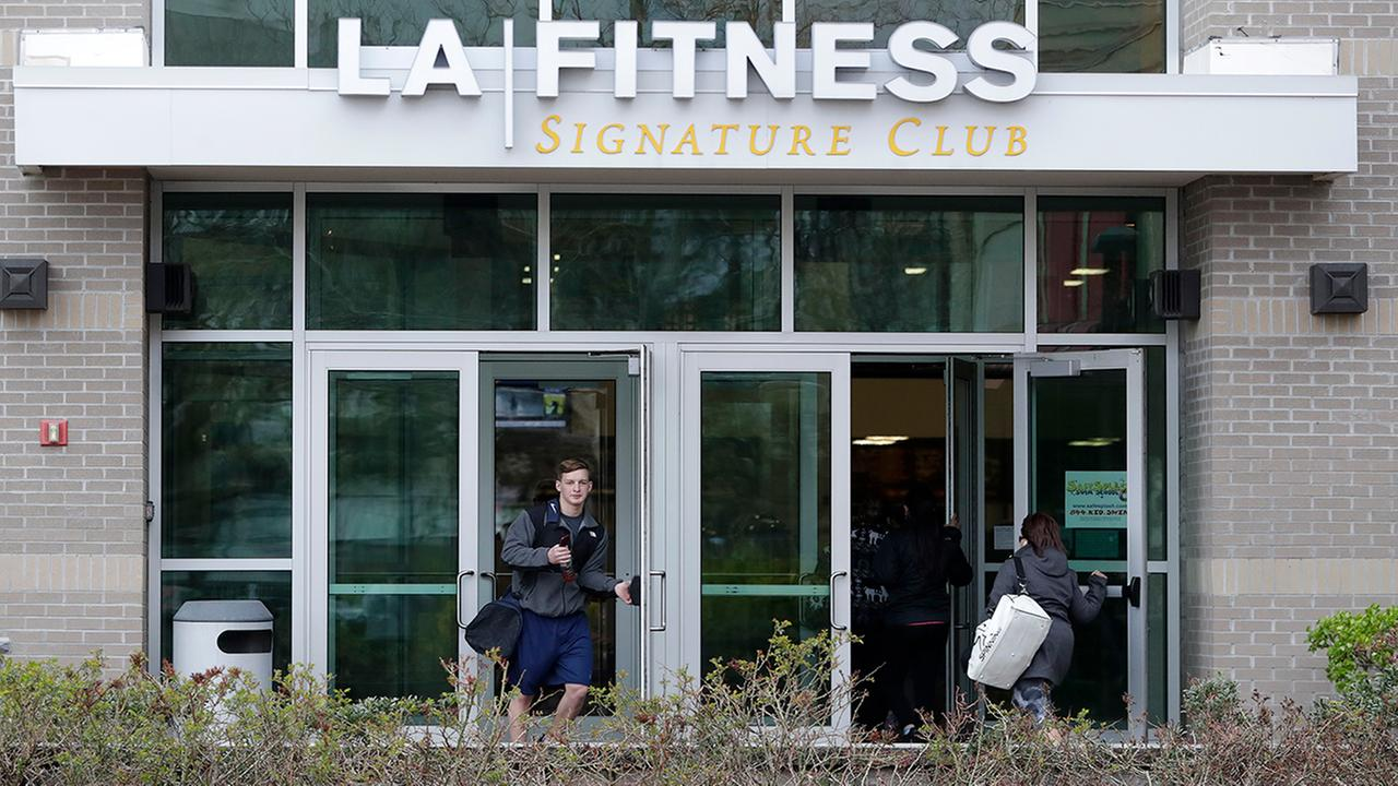 A person, left, leaves an LA Fitness gym while a group of women, right, enter the club, Thursday, April 19, 2018, in Secaucus, N.J.  (AP Photo/Julio Cortez)