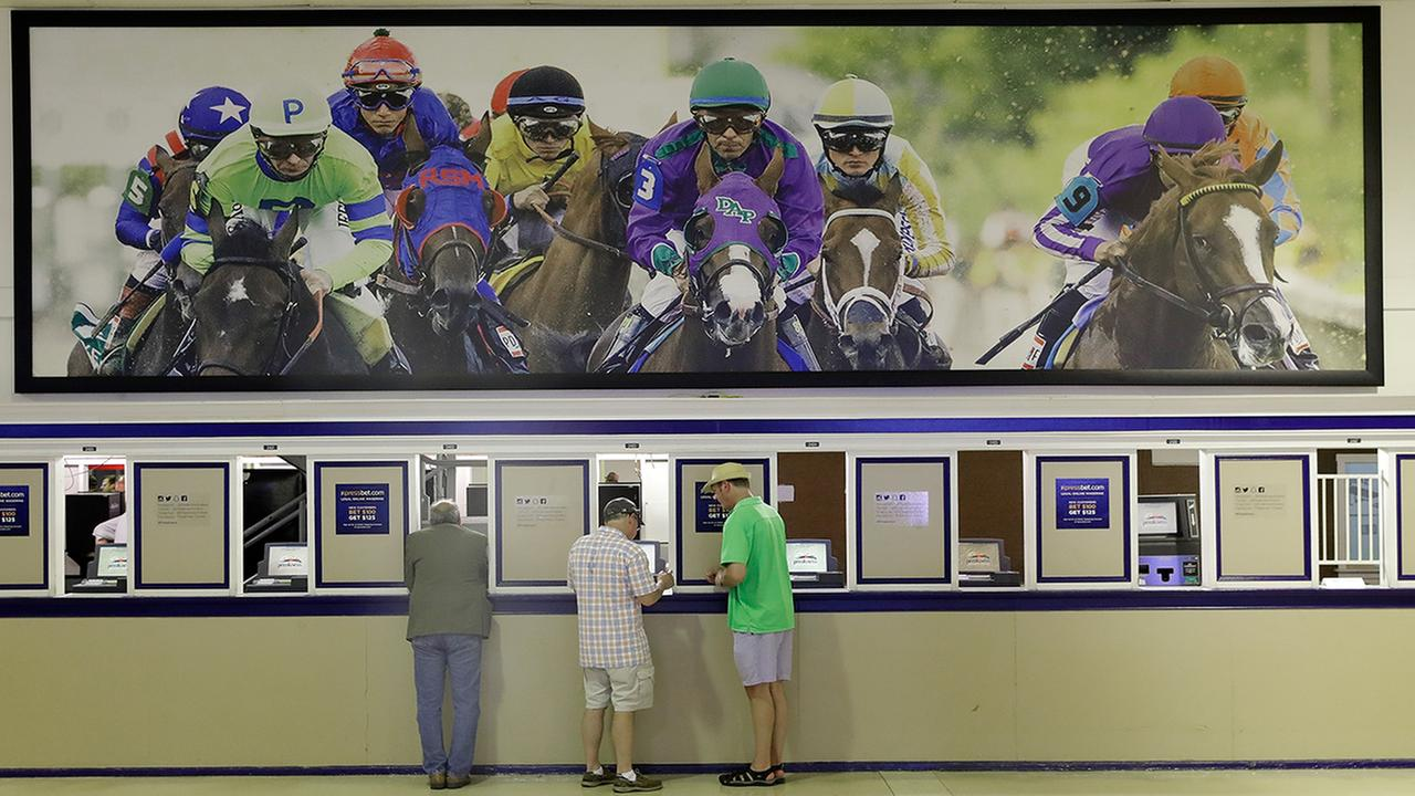 In this May 19, 2017 file photo, fans place bets ahead of the running of the Black-Eyed Susan horse race at Pimlico race course in Baltimore.  (AP Photo/Patrick Semansky, File)