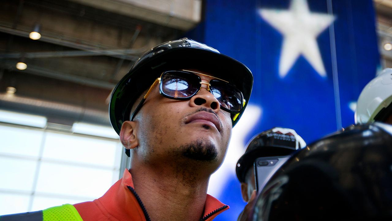 In this Tuesday, April 25, 2017, photo, rapper T.I. tours the Mercedes Benz Stadium, the new stadium for the Atlanta Falcons. (AP Photo/David Goldman)