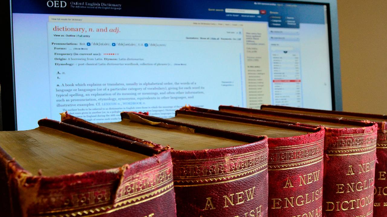 This image from the Oxford English Dictionary shows old volumes next to a computer displaying a page from the Oxford English Dictionary website. (Oxford English Dictionary via AP)
