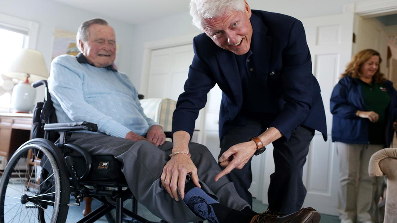 Bill Clinton jokes with George H.W. Bush as Bush shows off a pair of Bill Clinton socks, while Clinton visits Bush in Maine. (Evan F. Sisley/Office of George Bush via AP)
