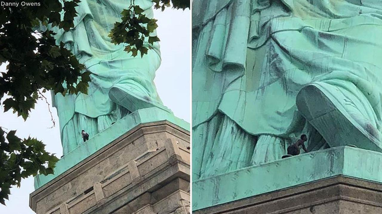 Person climbing the Statue of Liberty