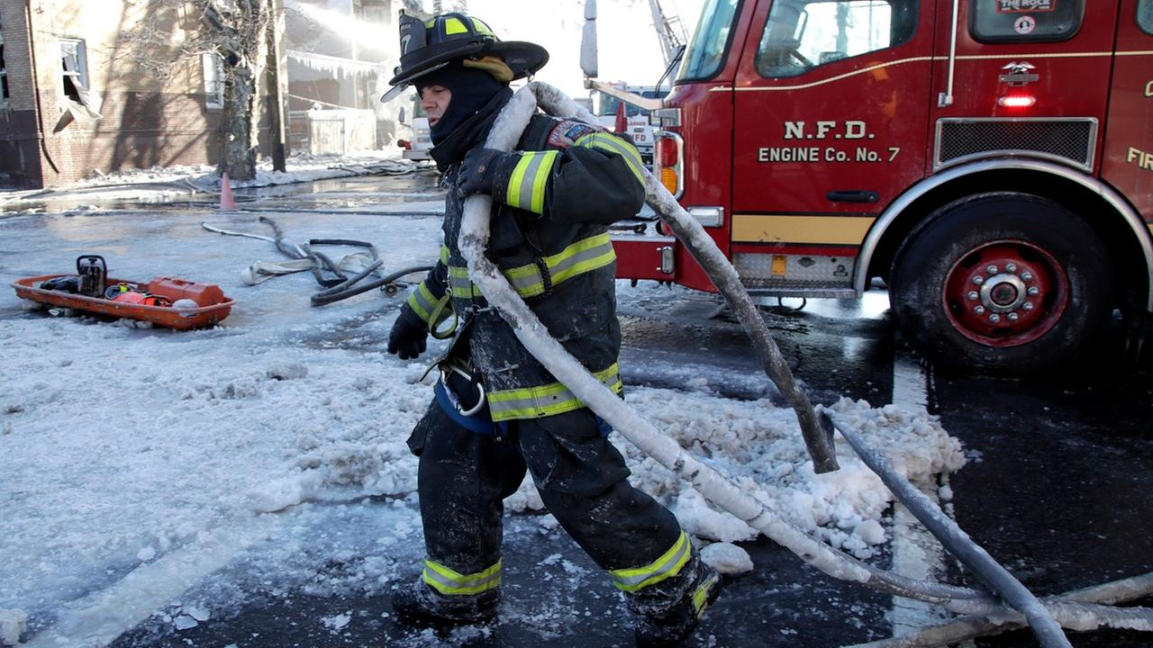 In this Jan. 5, 2018 file photo, a Newark firefighter pulls a hose back onto an engine after helping battle a five building fire in Newark, N.J.